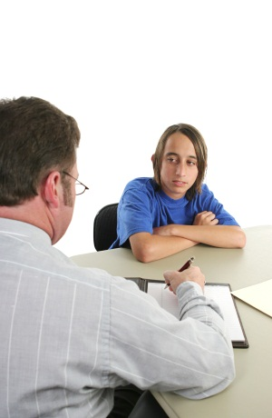 A teacher discussing falling grades with an angry teen student.